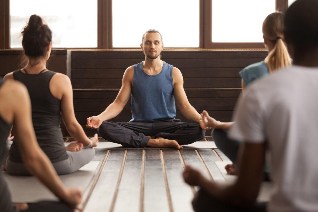 Groep van jonge sportieve mensen in meditatie houding